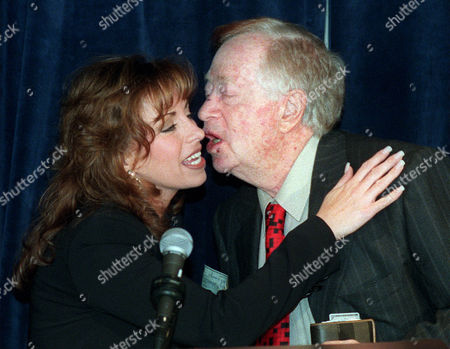 JONES HIRSHFELD Paula Jones gets a kiss from New York real estate tycoon Abe Hirschfeld after he presented her a check for $1 million during a news conference at a Washington Hotel . The money would become part of an overall settlement of Jones's sexual harassment suit against President Clinton, though a spokeswoman for the former Arkansas state worker said there was no deal yet