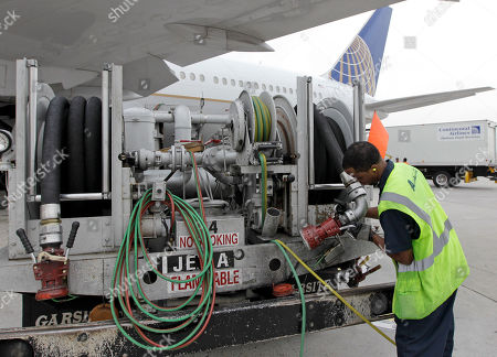 Continental Airlines Louis Williams returns a hose to a fuel truck after fueling a Continental Airlines plane at George Bush Intercontinental Airport in Houston. Continental is part of the global Star Alliance network