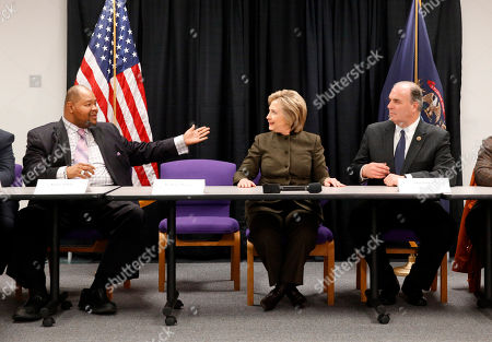 Hillary Clinton Kerry Nelson, left, Flint City Council President, motions to Democratic presidential candidate Hillary Clinton as Rep. Dan Kildee, D-Mich., listens during a meeting with officials at the House Of Prayer Missionary Baptist Church, in Flint, Mich
