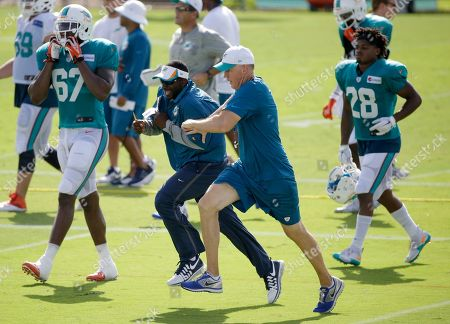 Joe Philbin, Blue Adams Miami Dolphins head coach Joe Philbin, foreground center, races assistant defensive backs coach Blue Adams as they change practice fields at the teams NFL football training camp, in Davie, Fla