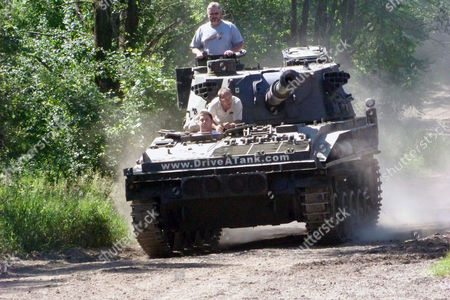 In this photo made, Nick Walker of Amboy, Indiana drives an armored vehicle in Kasota, Minn., while his father Brad Walker looks out from the turret and Drive A Tank owner Tony Borglum sits behind him. For a fee, Drive A Tank gives people a chance to drive a tank or armored vehicle around a mile-long dirt course and to crush a car with a tank