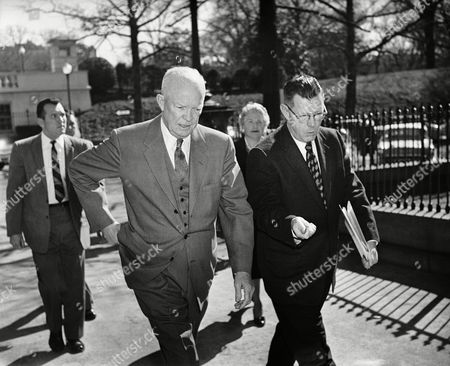Stock Picture of President Dwight Eisenhower and his Press Secretary James Hagerty, engage in some serious conversation on in Washington as they walk from the White House to the nearby Executive Offices Building for the Chief executive's weekly press conference. In the background is Anne Wheaton, of the Associates Press