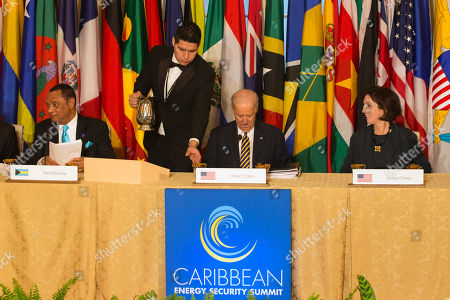 Stock Image of Joe Biden, Perry Christie, Roberta Jacobson A waiter pours water for Vice President Joe Biden, center, next to Bahamas Prime Minister Perry Christie, left, and State Department Assistant Secretary of State for Western Hemisphere Affairs, Roberta Jacobson, as they attend a multilateral meeting with leaders at the Caribbean Energy Security Summit, at the State Department in Washington