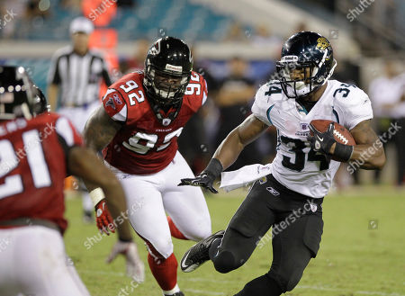 Jacksonville Jaguars running back Richard Murphy (34) looks for a way around Atlanta Falcons defensive end Chauncey Davis (92) during the second half of an NFL preseason football game, in Jacksonville, Fla