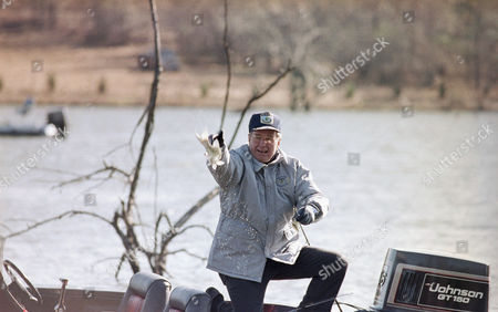 U.S. President George H. Bush removes the hook from a small bass he caught, during a New Year's Day fishing trip with angler Ray Scott in Pintlala. Bush released the fish First Lady Barbara Bush also was along on the trip and caught a bass