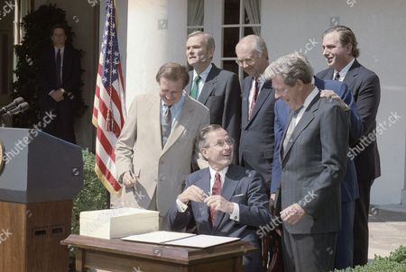 U.S. President George H. Bush talks with to Rep. Chalmers Wylie, R-Ohio, during a ceremony in the Rose Garden of the White House on in Washington bailing out the savings and loan industry. From left are: Sen. Don Riegle D-Mich.; Treasury Secretary Nicholas Brady; Bush; Sen. Phill Gramm, R-Texas; Wylie and Budget Director Richard Darman. Rep. Henry Gonzales, D-Texas, is hidden behind Wylie