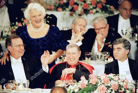 The Republican and Democratic candidates for president appear with New York?s Cardinal John J. O?Connor at the annual Alfred E. Smith dinner on in New York. Barbara Bush embraces her husband George Bush on the podium as she greets other guests. From left are: George H.W. Bush, Cardinal O?Connor, Michael Dukakis, New York Mayor Edward Koch and New Jersey Governor Thomas Kean
