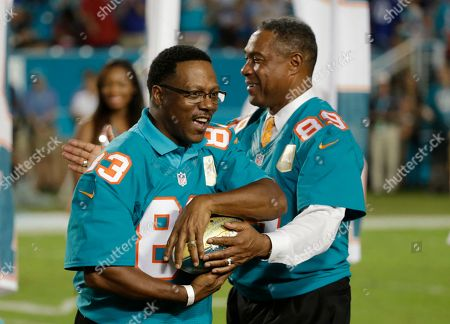 Mark Clayton, Nat Moore Former Miami Dolphins player Mark Clayton (83) is presented a football by former player and current Dolphins senior vice president of special projects and alumni relations, Nat Moore (89) during the Dolphins All-Time 50th Anniversary Team ceremony during half time at an NFL football game against the New York Giants, in Miami Gardens, Fla