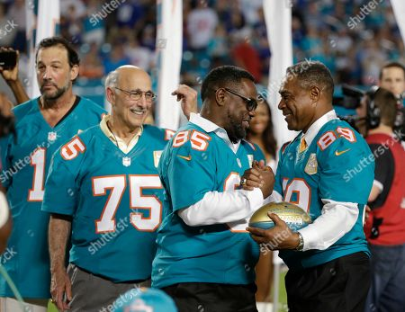 Mark Duper, Nat Moore Former Miami Dolphins player Mark Duper (85) is presented a football by former player and current Dolphins senior vice president of special projects and alumni relations, Nat Moore (89) during the Dolphins All-Time 50th Anniversary Team ceremony during half time at an NFL football game against the New York Giants, in Miami Gardens, Fla