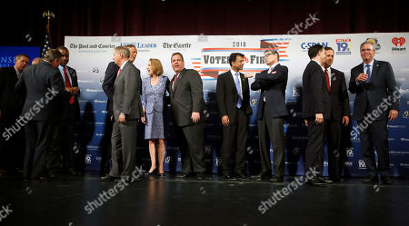 Republican presidential candidates John Kasich, left, Ben Carson, third from left, Lindsey Graham, George Pataki, Carly Fiorina, Chris Christie, Bobby Jindal, Rick Perry, Scott Walker, Rick Santorum and Jeb Bush speak among themselves after a forum, in Manchester, N.H. Second from left is Saint Anselm College president Steven DiSalvo