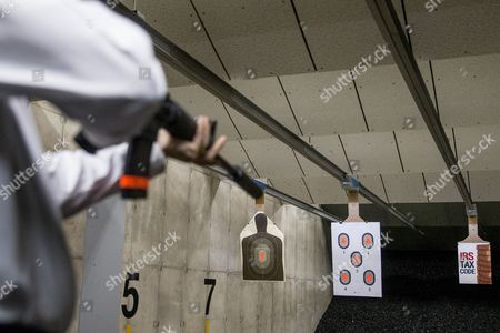 """Rand Paul Republican presidential candidate Sen. Rand Paul, R-Ky., fires an AR-15 rifle at an """"IRS Tax Code"""" poster at Crossroads Shooting Sports in Johnston, Iowa"""