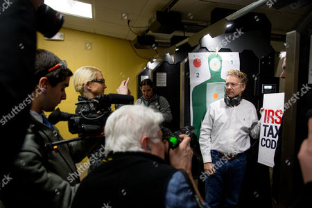 """Rand Paul Republican presidential candidate Sen. Rand Paul, R-Ky., poses with at an """"IRS Tax Code"""" poster after firing an AR-15 rifle at it at Crossroads Shooting Sports in Johnston, Iowa"""