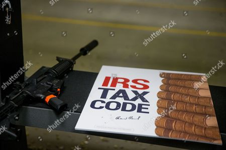 """Bullet holes can be seen in an """"IRS Tax Code"""" poster after Republican presidential candidate Sen. Rand Paul, R-Ky., fires an AR-15 rifle at it at Crossroads Shooting Sports in Johnston, Iowa"""