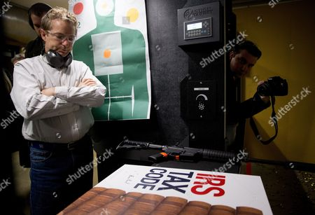 """Stock Picture of Rand Paul Republican presidential candidate Sen. Rand Paul, R-Ky., stands at a shooting range after firing an AR-15 rifle at an """"IRS Tax Code"""" poster at Crossroads Shooting Sports in Johnston, Iowa"""