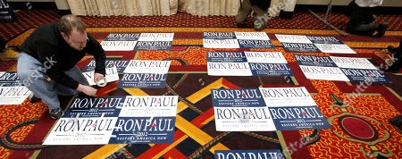 Matt Collins, a campaign staffer for Republican presidential candidate Rep. Ron Paul, R-Texas, tapes signs together before the North Dakota caucus, in Fargo, N.D
