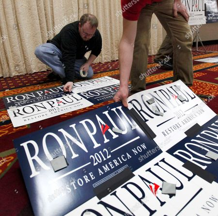 Matt Collins, a campaign staffer for Republican presidential candidate Rep. Ron Paul, R-Texas, helps tape signs together before the North Dakota caucus, in Fargo, N.D
