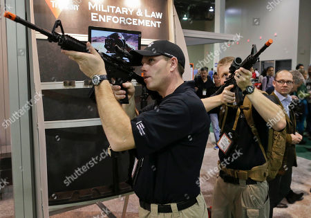 Brendan Vance, left, and Tom Beyer, co-owners of a tactical equipment and clothing store in Walla Walla, Wash., look through various rifle scopes at the 35th annual SHOT Show, in Las Vegas. The National Shooting Sports Foundation issued a statement Wednesday in Las Vegas calling it critical to keep firearms out of the hands of those it calls irresponsible and not legally qualified to possess them
