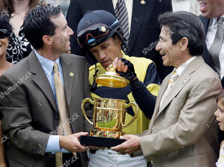 David Flores, Jeffrey Bloom, Laffit Pincay Jr Jockey David Flores examines the winner's trophy, with Jeffrey Bloom, a vice-president of West Point Thoroughbreds, left, and retired Hall of Fame jockey Laffit Pincay Jr., who presented the award, after Flores and Awesome Gem won the $500,000 Hollywood Gold Cup horse race at Hollywood Park in Inglewood, Calif