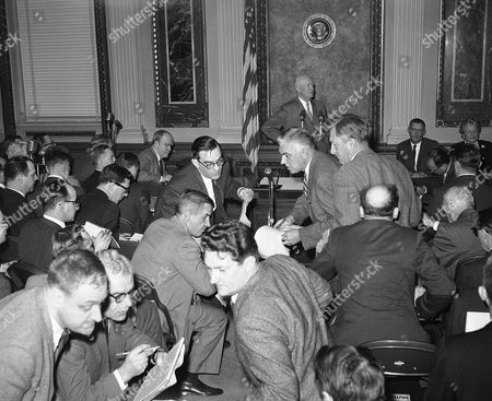 Stock Photo of Newsmen start to leave their seats to make their way to the door as the conference nears its end. The President answers a final question with Press Secretary James Hagerty, second from right, and associate press secretary Anne Wheaton seated at right along wall