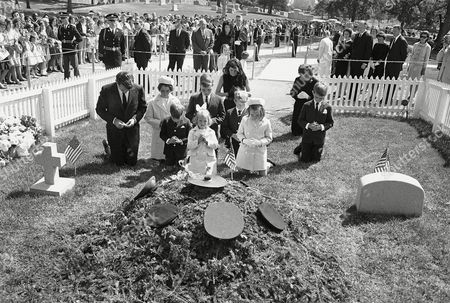 Attorney General Robert F. Kennedy and his family kneel at the grave of his brother, John F. Kennedy, in Arlington National Cemetery, the assassinated president's birthday. From left: Robert Kennedy; Kathleen, 12; Michael, 6; Joseph, 11; Mary Kerry, front, 4; Patricia Lawford; David, 8; Mary Courtney, 7; Ethel Kennedy, the senator's wife, and Robert Francis, 10. Jacqueline Kennedy and her children, Caroline and John, Jr., stand in center background