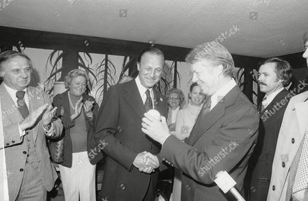 """Jimmy Carter holds a baseball presented to him by Stan """"The Man"""" Musial on during a campaign stop in St. Louis. Carter spent the night at a hotel owned by Musial and was scheduled to resume his last-minute campaign swing Saturday. Carter appeared at a rally at a suburban shopping center on Friday, Oct. 30, 1976. His visit came only hours after President Ford held a rally at a park in downtown St. Louis"""
