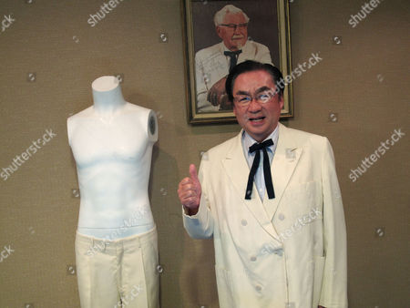 """Masao """"Charlie"""" Watanabe, president and chief executive of Kentucky Fried Chicken Japan, stands beneath a portrait of company founder """"Colonel"""" Harland Sanders, at Heritage Auctions in Dallas. Watanabe is wearing Sanders' trademark white suit jacket and black string tie after he purchased them at the auction, which featured other items, including leg irons that restrained abolitionist John Brown"""