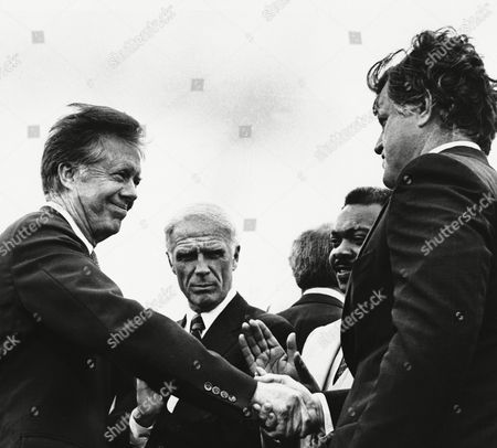 Sen. Edward M. Kennedy, right, welcomes President Jimmy Carter to Boston, . also at the Logan International Airport meeting are Boston's Mayor Kevin White, rear left, and Massachusetts Sen. William Owens (D-Boston). The president is in Boston to address the American Legion convention
