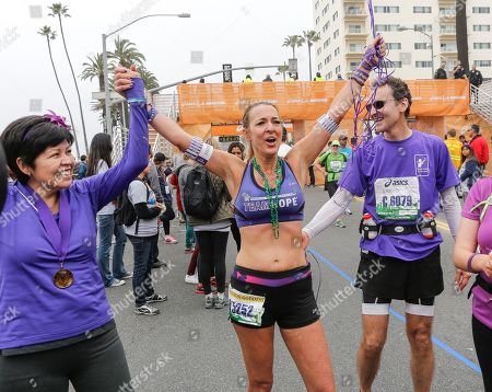 Lupe Romero, Julie Weiss, David Levine Julie Weiss, 42, center, with her fiancee David Levine, right, and six month pancreatic cancer survivor Lupe Romero, left, celebrate after Weiss completed her 52 marathons in 52 weeks, in dedication to her father who died from pancreatic cancer at age 75, in Santa Monica, Calif