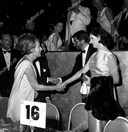 """George Hamilton, Lynda Bird Johnson Lynda Bird Johnson and her escort, actor George Hamilton, are greeted by actress Irene Dunne, left, and Jules Styne, almost Hidden, top Universal Studio executive, as they arrive at a swank society benefit ball in Los Angeles, . Hamilton wears a beard for his role in a movie, The Long Ride Home,"""" currently being filmed in Utah"""