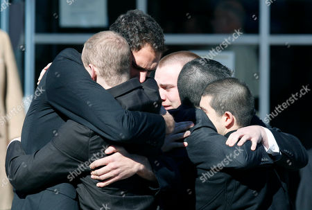 Stock Picture of Mourners hug outside a memorial service for Brendan Burke, the son of President and General Manager of the Toronto Maple Leafs Brian Burke, in Canton, Mass