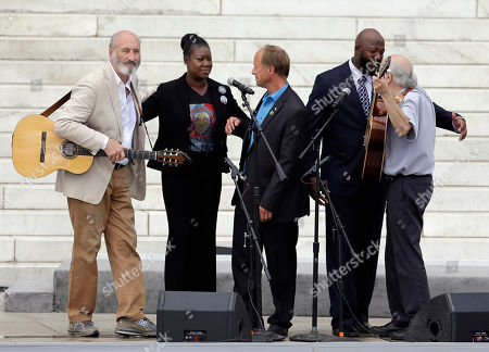 With Trayvon Martin parents, Sybrina Fulton, and Tracy Martin, and Mark Barden, father of Sandy Hook Elementary School shooting victim Daniel Barden, Peter Yarrow, left, and Paul Stookey, right, of the folk trio Peter, Paul and Mary, perform at the 50th Anniversary of the March on Washington where Martin Luther King, Jr., spoke, in front of the Lincoln Memorial in Washington