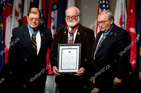 Stock Photo of Michael Reagan, Michael Fitzmaurice, Harold Fritz Michael G. Reagan a Vietnam veteran from Edmonds Wa., is presented by Medal of Honor recipient Michael Fitzmaurice, right, and Congressional Medal of Honor Society President and Medal of Honor recipient Harold Fritz, left, with Citizen Service Before Self Honors during a ceremony at Arlington National Cemetery, in Arlington, Va., in honor of National Medal of Honor Day 2015. Reagan was selected for his service in founding the non-profit Fallen Heroes Project, which provides hand-drawn portraits to families of al servicemen and women who have been killed in Iraq and Afghanistan