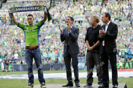 Clint Dempsey, Joe Roth, Adrian Hanauer, Peter McLoughlin Clint Dempsey, left, captain of the United States Men's National Soccer Team, raises a Seattle Sounders scarf as he is introduced as the newest member of the team by Sounders owner Joe Roth, second from left, Sounders general manager Adrian Hanauer, second from right, and Sounders president Peter McLoughlin, right, during a ceremony, prior to a MLS soccer match between the Sounders and FC Dallas in Seattle. Dempsey previously played for Tottenham Hotspur in the English Premier League