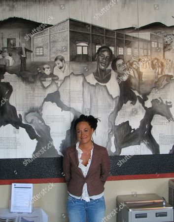 Rachel Dolezal, a leader of the Human Rights Education Institute, stands in front of a mural she painted at the institute's offices in Coeur d'Alene, Idaho. Dolezal, now president of the Spokane, Wash., chapter of the NAACP, is facing questions about whether she lied about her racial identity, with her family saying she is white but has portrayed herself as black