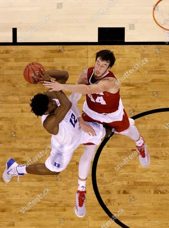 Duke's Justise Winslow (12) gets fouled by Wisconsin's Frank Kaminsky (44) during the first half of the NCAA Final Four college basketball tournament championship game, in Indianapolis