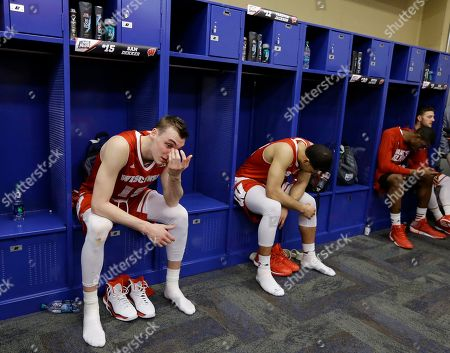 Wisconsin's Sam Dekker, left, and Traevon Jackson sit in the locker room after their team's 68-63 loss to Duke in the NCAA Final Four college basketball tournament championship game, in Indianapolis