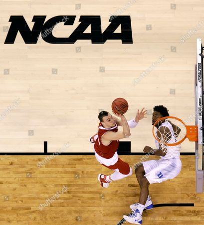 Wisconsin's Sam Dekker drives to the basket over Duke's Justise Winslow during the second half of the NCAA Final Four college basketball tournament championship game, in Indianapolis