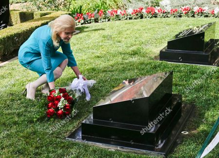 Stock Photo of Tricia Nixon Cox daughter of the 37th U.S. President Richard M. Nixon lays flower on his head stone during a ceremony honoring the 100th anniversary of the birth of Richard Nixon at the Richard Nixon Presidential Library in Yorba Linda, Calif
