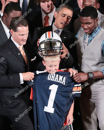 Barack Obama, Gene Chizik, Kodi Burns, Ethan Gibbs President Barack Obama puts a team helmet on Ethan Gibbs, son of former White House Press Secretary Robert Gibbs, in the East of the White House in Washington, during a ceremony honoring the 2010 NCAA BCS Football Champion Auburn Tigers. With Obama are Head coach Gene Chizik, left, and player Kodi Burns is at right