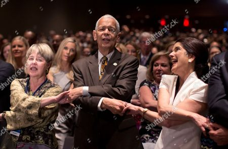 """Julian Bond, Luci Baines Johnson Social activist Julian Bond, center, and Luci Baines Johnson, the younger daughter of President Lyndon Baines Johnson, right join hands as they sing """"We Shall Overcome"""" before President Barack Obama speaks at the LBJ Presidential Library, in Austin, Texas, during the Civil Rights Summit to commemorate the 50th anniversary of the signing of the Civil Rights Act"""