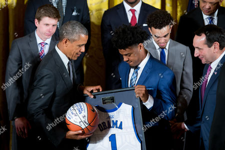 Barack Obama, Quinn Cook, Mike Krzyzewski Duke Blue Devils guard and co-captain Quinn Cook, center right, accompanied by Duke head coach Mike Krzyzewski, right, presents President Barack Obama a signed basketball and jersey in the East Room of the White House in Washington, during a ceremony honoring the NCAA Champion Duke Blue Devils men's basketball team