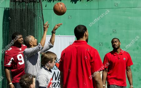 Barack Obama, John Wall, Calais Campbell President Barack Obama shoots a basket as he plays on the basketball court on the South Lawn of the White House in Washington during the White House Easter Egg Roll, . Thousands of children gathered at the White House for the annual Easter Egg Roll. This year's event features live music, cooking stations, storytelling, and of course, some Easter egg roll. Washington Wizards basketball player John Wall watches at right, Arizona Cardinals football player Calais Campbell is at left