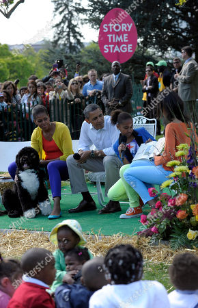 """Barack Obama, Malia Obama, Sasha Obama, Michelle Obama, Bo President Barack Obama, first lady Michelle Obama and Bo, listens as his daughters Sasha, center, and Malia, right, read """"A Sick Day for Amos McGee,"""" during the annual White House Easter Egg Roll, on the South Lawn of the White House in Washington"""