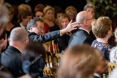 Yo-Yo Ma Chinese American cellist Yo-Yo Ma, left, jokingly touches the back of an unidentified man's head before the start of the 2015 Kennedy Center Honors reception in the East Room of the White House, in Washington. The 2015 Kennedy Center Honors Honorees are singer-songwriter Carole King, filmmaker George Lucas, actress and singer Rita Moreno, conductor Seiji Ozawa, and actress Cicely Tyson
