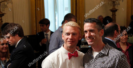 "Daniel Keenan Savage, Terry Miller Syndicated columnist Daniel Keenan ""Dan"" Savage, right, poses for a photo with his husband Terry Miller, left, as they wait for President Barack Obama to speak at the LGBT Pride Month event in the East Room of the White House in Washington"