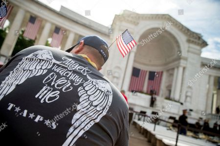 Chris Payne Chris Payne of Kalama, Wash. wears a Tragedy Assistance Program for Survivors (TAPS) shirt depicting wings on his back as he and other guests wait for President Barack Obama to speak at the Memorial Amphitheater of Arlington National Cemetery, in Arlington, Va., during a Memorial Day ceremony. Payne is here in memory of Army Spc. Eric D. King who was killed in Baghdad in 2006