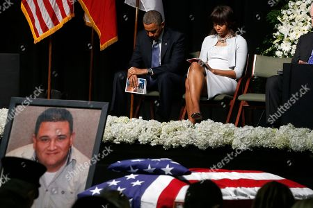 Barack Obama, Michelle Obama President Barack Obama and first lady Michelle Obama bow their heads behind a photo of volunteer firefighter Capt. Cyrus Adam Reed, who was killed, as they attend the memorial for victims of the fertilizer plant explosion in West, Texas, at Baylor University in Waco,Texas