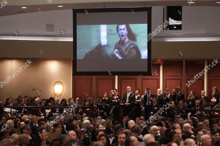 """Audience members watch as screenwriter Randall Wallace, not pictured, shows a clip from the movie """"Braveheart"""" starring Mel Gibson, before he spoke at the National Prayer Breakfast, attended by President Barack Obama, in Washington"""