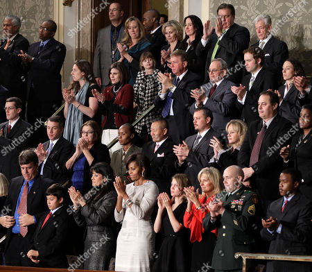 Stock Picture of Michelle Obama First lady Michelle Obama and guests applaud during President Barack Obama's State of the Union address in Washington, . Sitting in the first lady's box from front left are John Green, Dallas Green, Roxanna Green, Obama, Brianna Mast, Jill Biden, Sgt. Brian Mast and Brandon Ford. Second row from second to the left are Kathy Proctor, Sgt. Nicole Mohabir, Dr. Peter Rhee, Brandon Fisher, Julie Fisher, Gary Allen and Ursula M. Burns. Third row second from right is Zachary Davis and at right is Kendra Baker