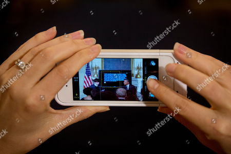 Stock Image of Barack Obama, David Karp A woman takes a cell phone photograph of President Barack Obama, right, during a Tumblr forum from the State Dining Room of the White House in Washington, moderated by Tumblr Founder and CEO David Karp, left